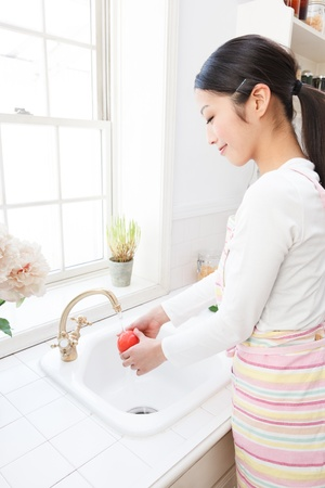 sterilization: Young Asian women wash the tomatoes in the sink by the window Stock Photo
