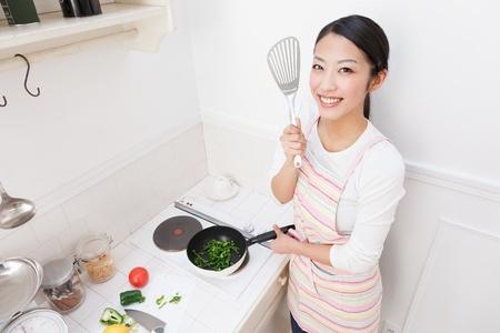 若いアジアの女性が台所で調理するには 写真素材