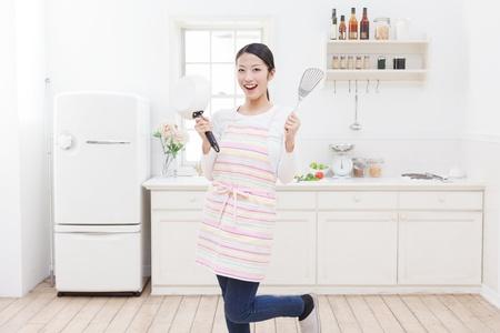 Junge asiatische Frau mit Kochutensilien in der K�che