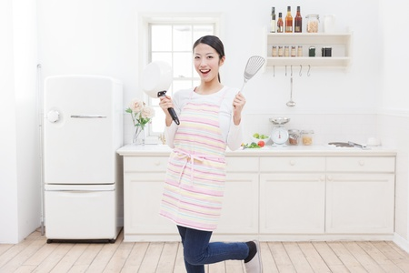 pan asian: Young Asian woman with cooking utensils in the kitchen