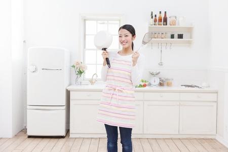 ama de casa: La mujer joven asiática con utensilios de cocina en la cocina Foto de archivo