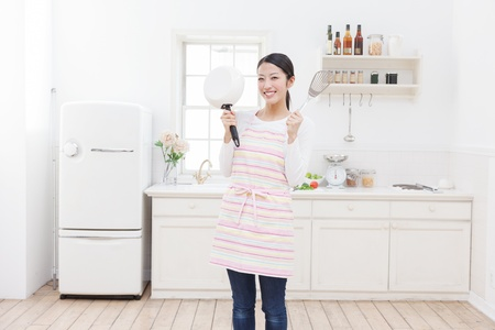 refrigerator kitchen: Young Asian woman with cooking utensils in the kitchen