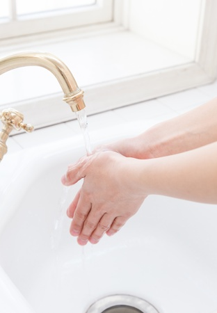 Hand-washing sink in the hands of a woman by the window Stock Photo