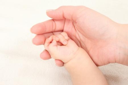 Asiatische Eltern und Kinder an den H�nden halten in wei�em Hintergrund