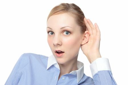 la escucha activa: Joven atractiva chica rubia sorprendido y escuchando atentamente la mano ahuecada alrededor de su oreja.