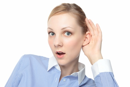 young  cuffs: Young attractive blond girl shocked and listening intently her hand cupped around her ear.