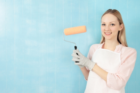 Young attractive smiling, blond  woman holding  paint roller with a blue tiled background  photo