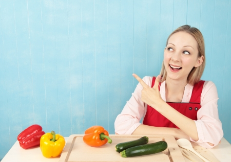 Attractive young woman sitting at  the kitchen table preparing peppers and corgettes with blue tiled background  Stock Photo - 14347026