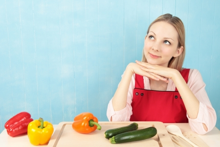 Young attractive woman sitting at the kitchen table with peppers and corgettes thinking about a recipe with a blue tiled background.  photo