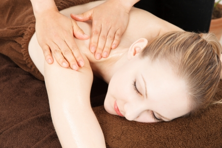 Relaxed woman receiving back massage at spa photo