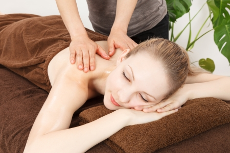 prone: Relaxed woman receiving back massage at spa