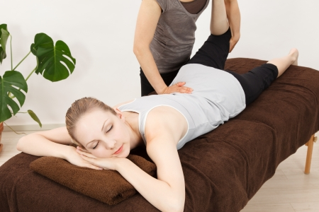 adjustment: Caucasian woman undergoing a chiropractic Stock Photo