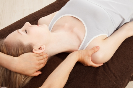 osteopathy: Beautiful young caucasian woman undergoing a massage Stock Photo