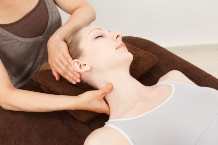 neck massage: Beautiful young caucasian woman undergoing a massage Stock Photo