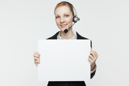 copys pace: Pretty, smiling woman wearing a headset and holding a blank sign.