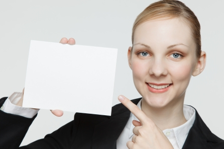 Attractive young businesswoman blank sign with copy space, studio background. photo