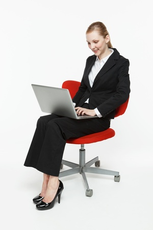 isolated chair: Smiling young businesswoman with laptop sitting in a chair