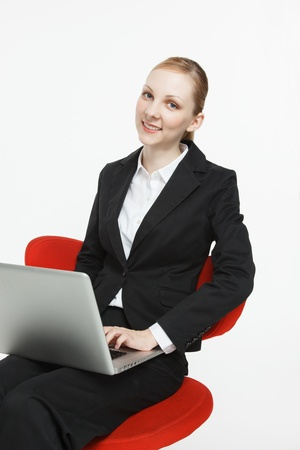 Smiling young businesswoman with laptop sitting in a chair photo