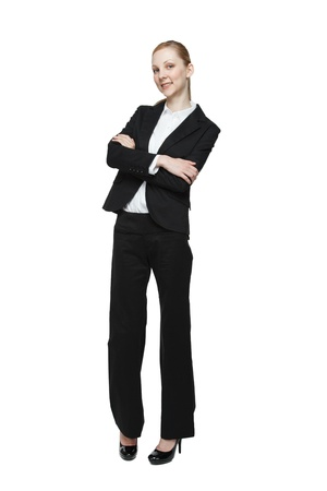 Fashionable young businesswoman with arms folded, white studio background. photo