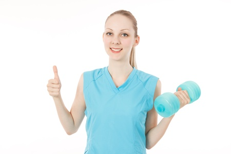 Young caucasian female fitness model with a dumbbell to make a finger  photo