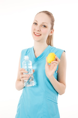Young caucasian female fitness model with the water and lemon on white backgrounds photo