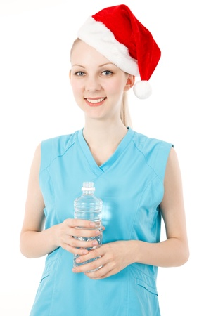 Young caucasian female fitness model with water wearing a santa hat photo