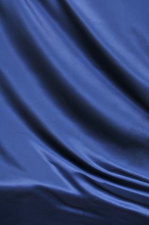エレガントなブルー シルクの滑らかな背景として使用することができます。 写真素材