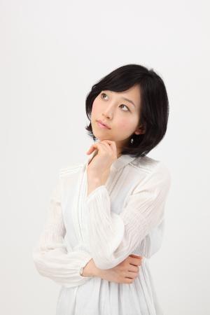白い背景の美しい若い日本の女性だと思う 写真素材