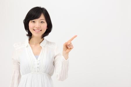 白い背景で日本の若い女性を指す 写真素材
