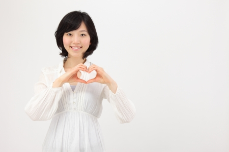 margins: Beautiful young japanese woman making heart with hands in white background Stock Photo