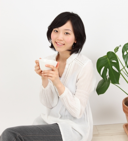 Beautiful young japaese woman relax with a cup in white background photo