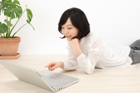 Beautiful young asian woman to a PC at home  Stock Photo - 18342210