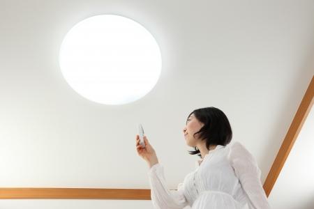 アジアの若い女性が電灯のスイッチを押されました。 写真素材