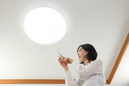 fluorescent lamp: Young Asian women pressed the light switch