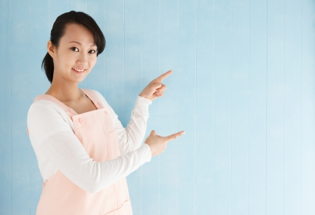 half body: Half body portrait of beautiful young japanese woman wearing an apron pointing with blue tiled background and copy space.