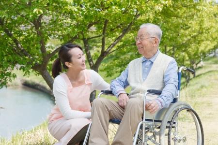 persona en silla de ruedas: Cuidadores japoneses y sonrisa de alto nivel en el campo
