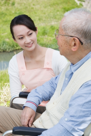 Senior man sitting on a wheelchair with caregiver photo