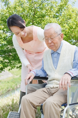 healthcare facilities: Asian senior man sitting on a wheelchair with caregiver Stock Photo