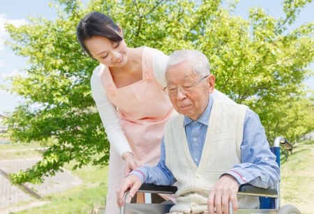 nursing assistant: Asian senior man sitting on a wheelchair with caregiver Stock Photo