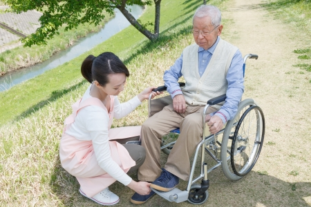 wheelchair man: Japanese caregivers and senior in the field Stock Photo