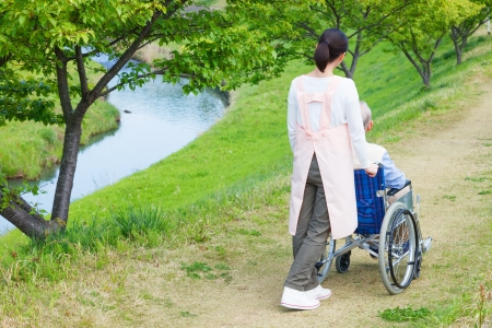 hospice: Asian senior man sitting on a wheelchair with caregiver