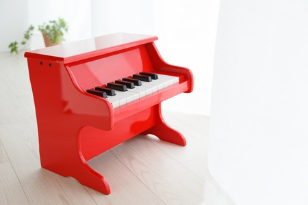 Miniature piano placed by the window photo