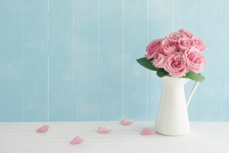 Rose geplaatst op het bureau in blauwe achtergrond Stockfoto