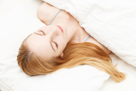 Beautiful young caucasian woman sleeping on the bed photo
