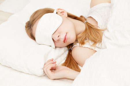 blinders: Beautiful young caucasian woman sleeping on the bed