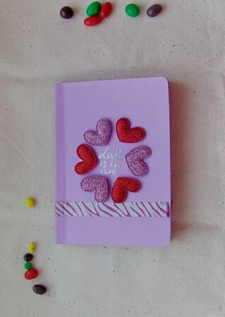 pink notepad with hearts in center photo top view around polka dot colored candy is all on canvas light