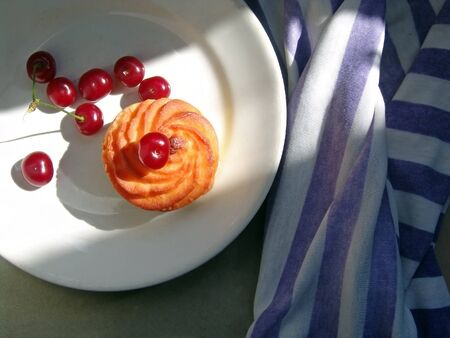 cherries and cupcake on a white round plate it is on the table with a striped fabric top view falls side contrast light along the photo....