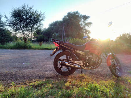Red motorcycle in the countryside on a background of trees and sunset in summer