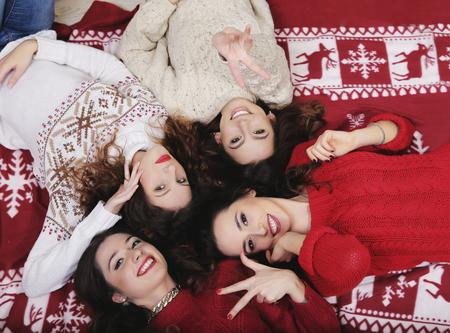 mujeres juntas: Grupo sonriente amigas feliz en el suéter de Año Nuevo que se acuesta en el suelo cerca Divertirse juntos en invierno tiempo de vacaciones