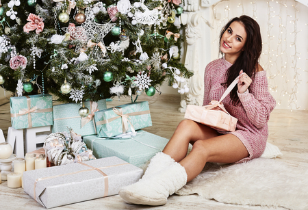 Young beauty smiling santa woman near the Christmas tree. Fashionable luxury girl celebrating New Year. Beautiful luxury trendy brunette